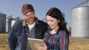 Man and woman in a field looking at an iPad