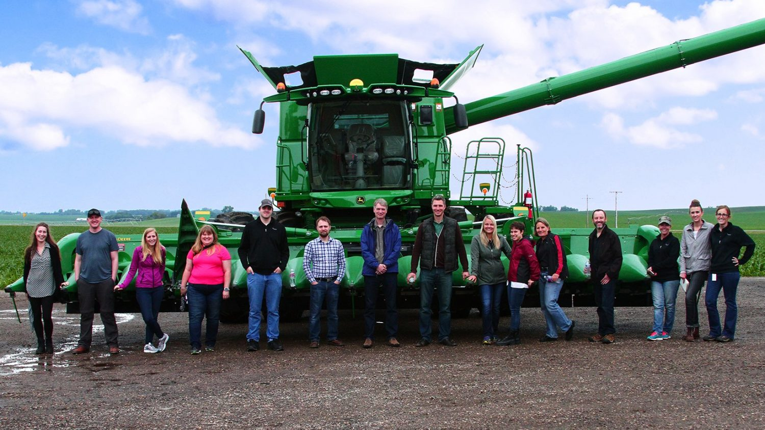 A group of people standing on a farm in front of a combine