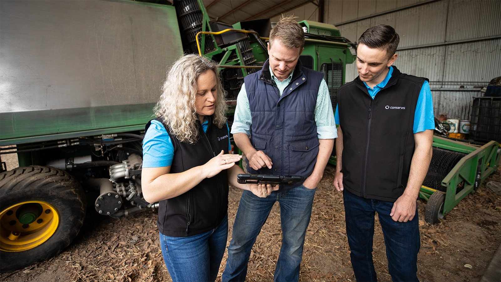 Conservis Customer Success standing with a customer on farm performing services with a tablet