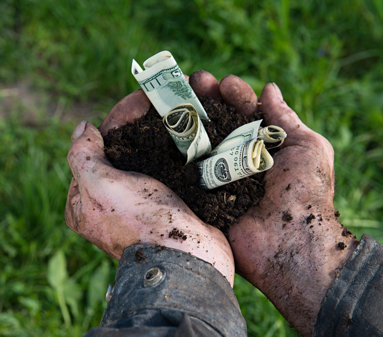Farmer holding soil with dollars