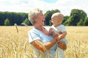 Grandmother with a grandchild standing in a wheat field