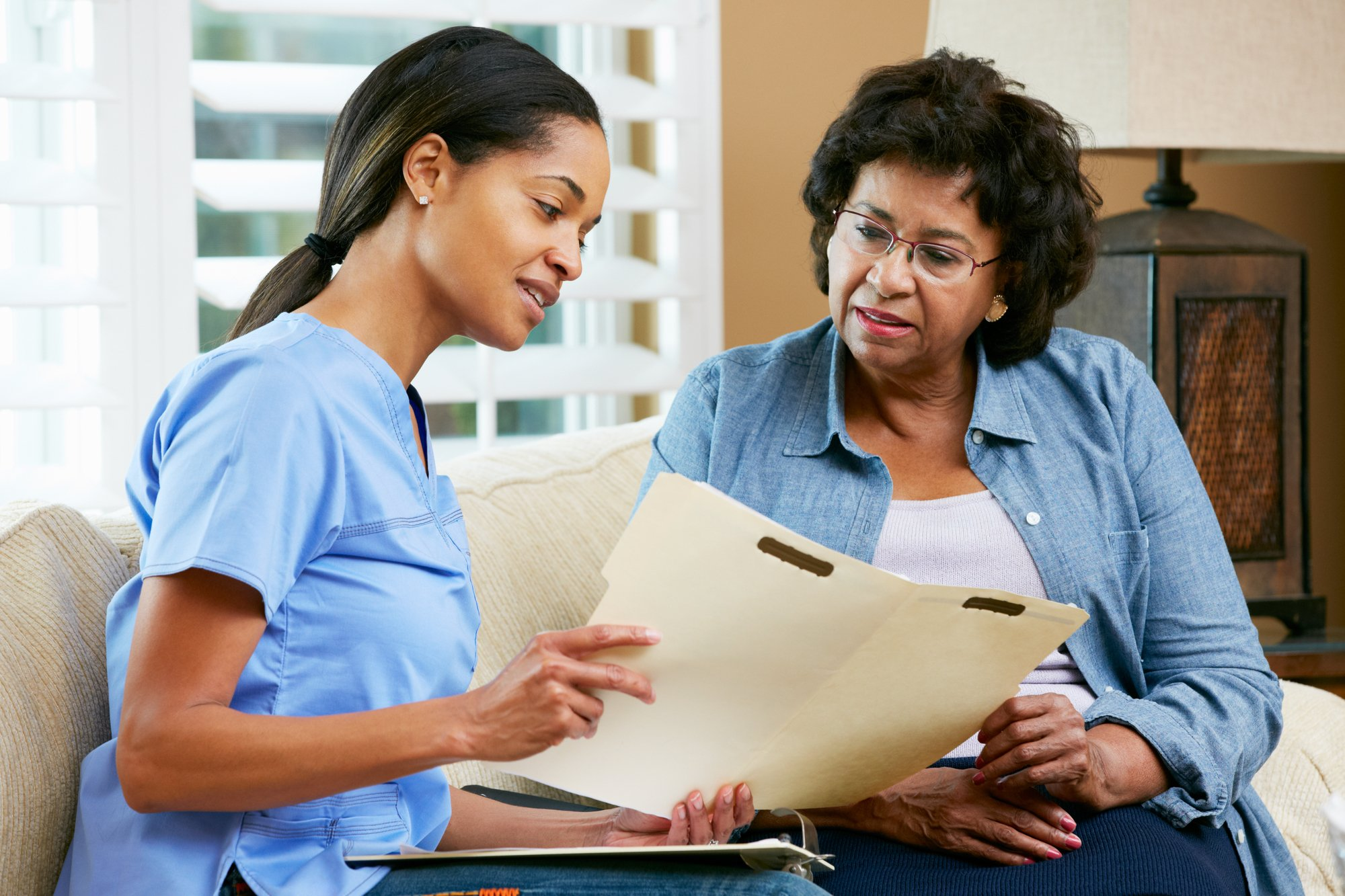 Doctor discussing records with senior Female patient in a healthcare setting