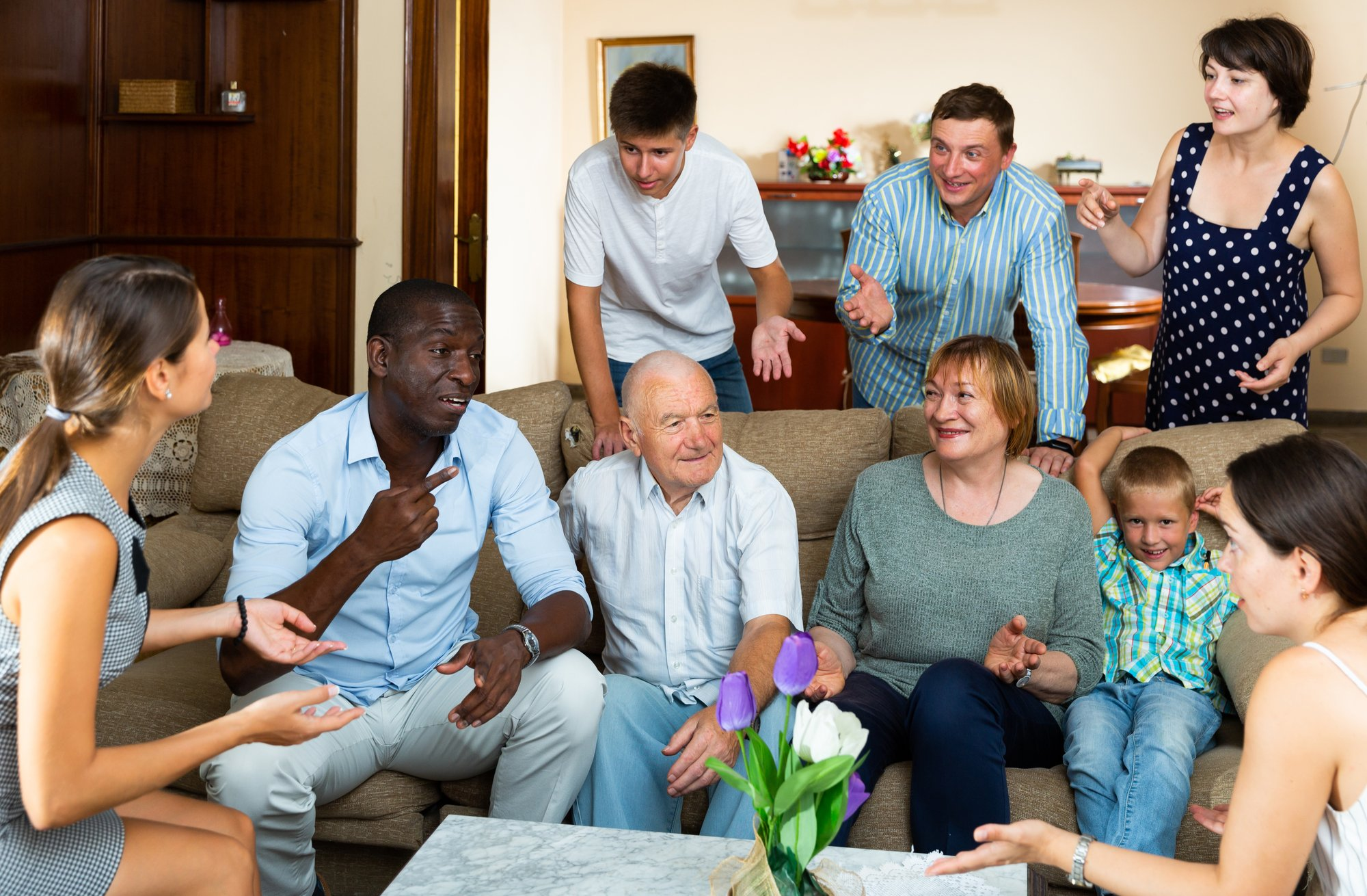 Large family with grandparents and children having meeting at home